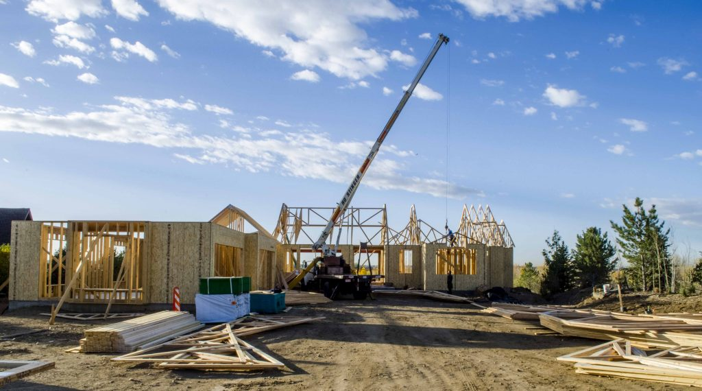 Crane lifting rafters into place on new home construction