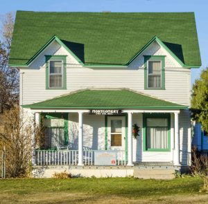 White two story farmhouse with green roof.